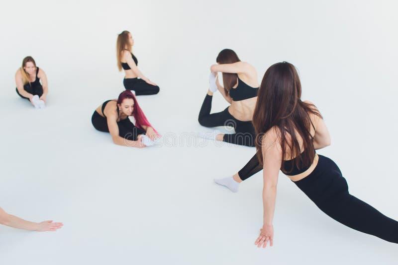健身,舒展实践,解决在体育俱乐部的小组两名可爱的愉快的微笑的适合成熟妇女,做 库存照片