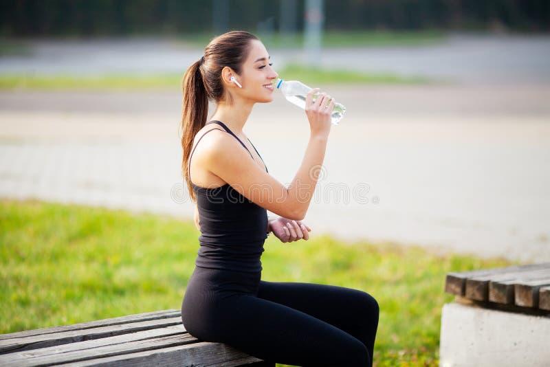 健身 体育和健康生活方式概念-在行使以后的妇女饮用水在公园 免版税库存照片