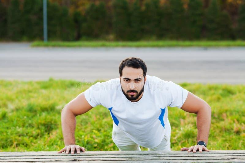 健身 在室外健身房的俯卧撑锻炼健身人训练胳膊肌肉 库存图片