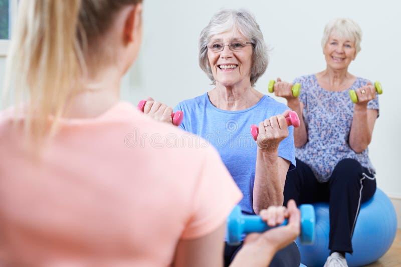 健身类的资深妇女与辅导员 免版税库存照片