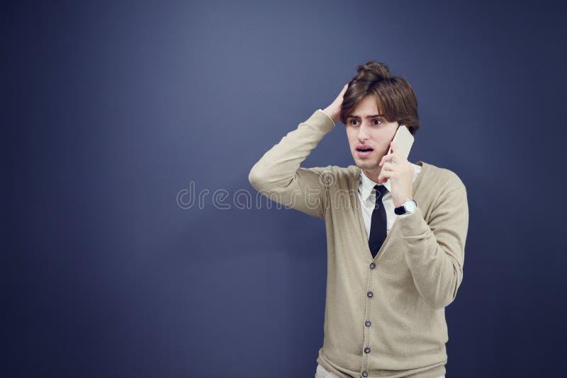 年轻偶然人谈话在白色背景隔绝的电话 免版税库存图片