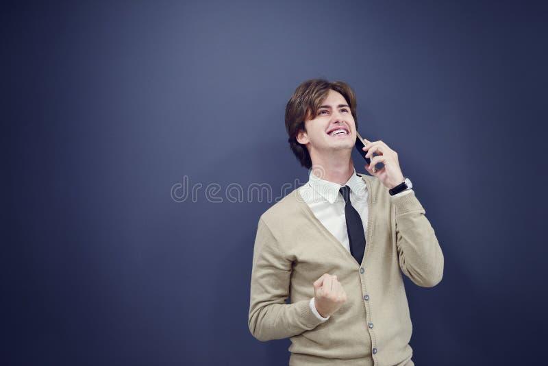 年轻偶然人谈话在白色背景隔绝的电话 库存照片