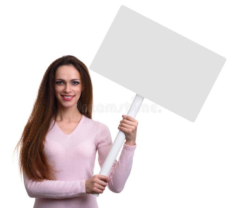 偶然俏丽的女孩举行一张空白的招贴 免版税库存图片