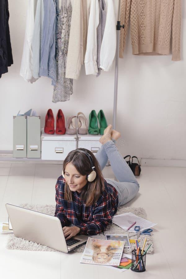 偶然博客作者妇女与膝上型计算机一起使用在她的时尚办公室。 免版税库存照片