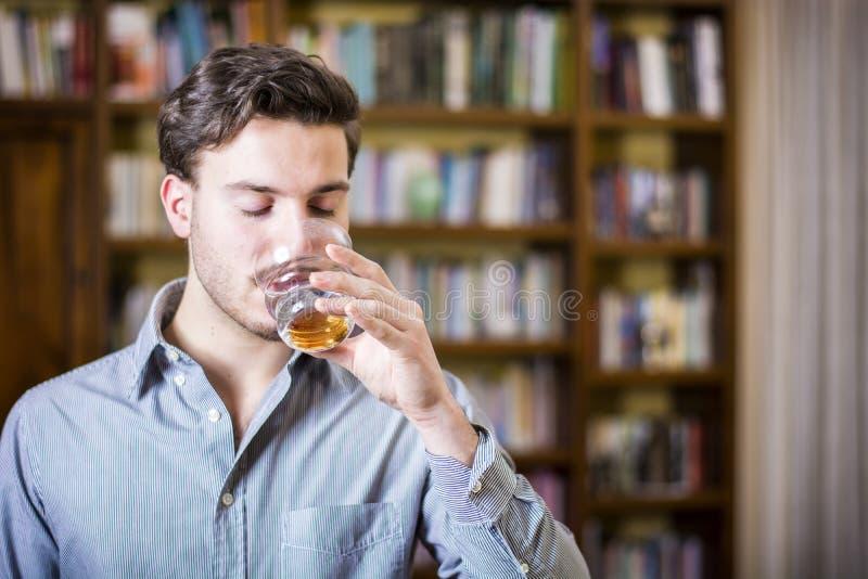 偶然可爱的年轻人饮用水在图书馆里 免版税图库摄影