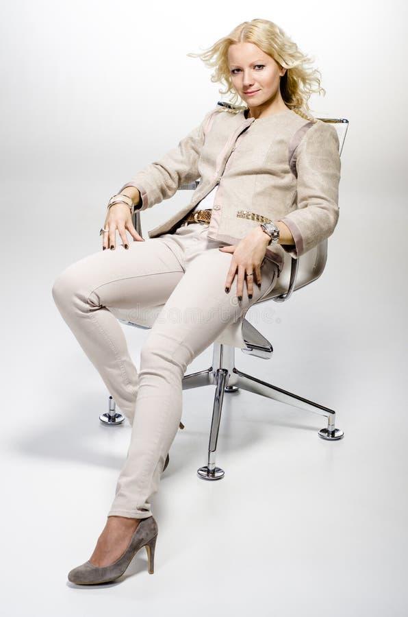 美丽的妇女坐椅子。 免版税图库摄影