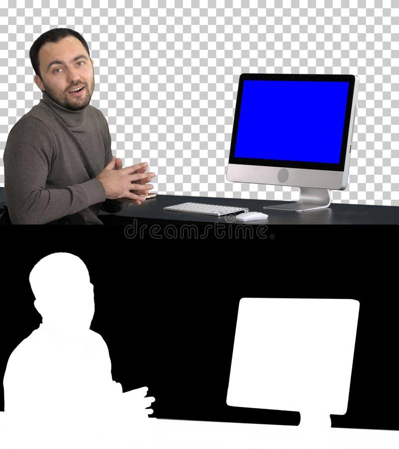 偶然商人微笑和谈话在显示某事在计算机,阿尔法通道显示器的照相机  蓝色 免版税库存图片