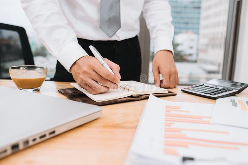偶然商人计划的工作计划,写与手提电脑和咖啡的笔记在桌在办公室 学生笔记 图库摄影