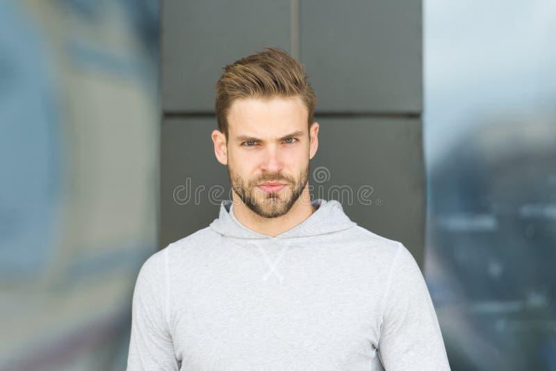 偶然在样式 有胡子的人在室外严肃的面孔 灰色运动衫的强壮男子在新鲜空气 详细的休假 免版税库存照片