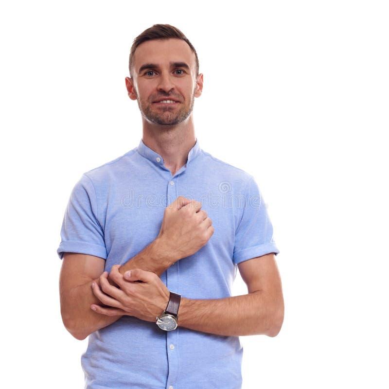 偶然地英俊 微笑牛仔裤的衬衣的确信的年轻英俊的人保持胳膊横渡和,当站立反对时 免版税库存图片