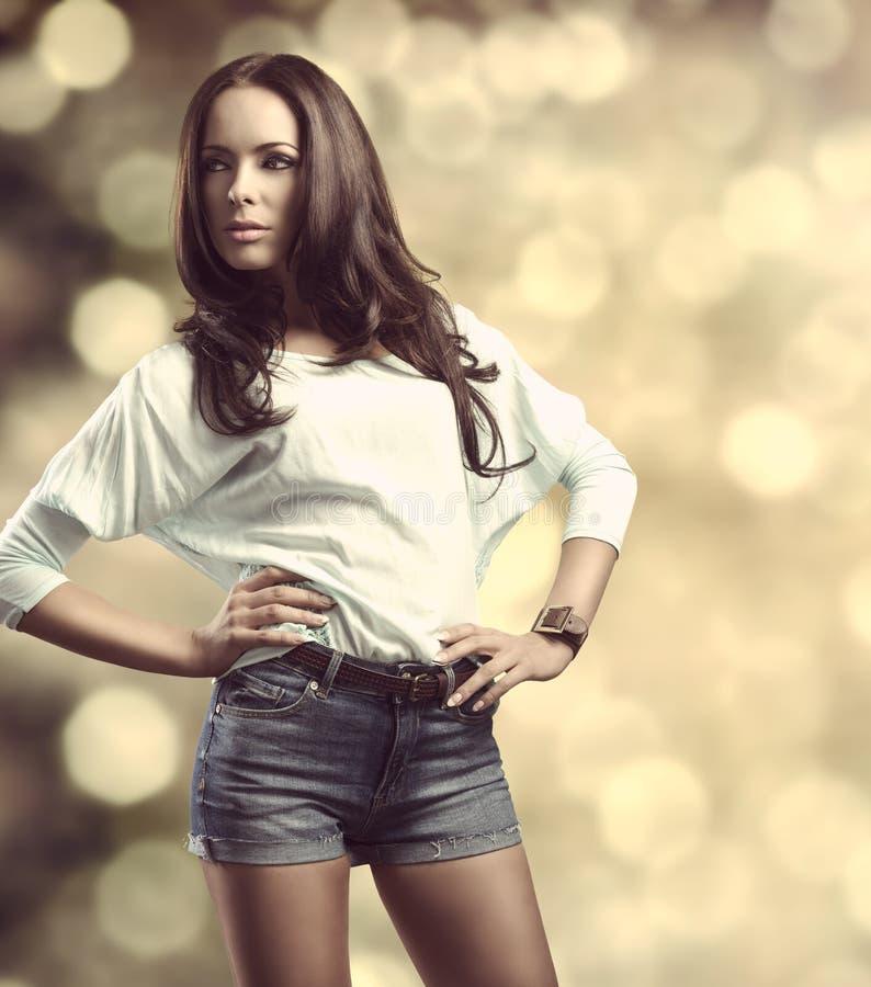 偶然女孩在时尚姿势bokeh背景中 免版税图库摄影