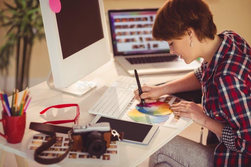 偶然女性设计师与数字化器和颜色图表一起使用 免版税库存照片