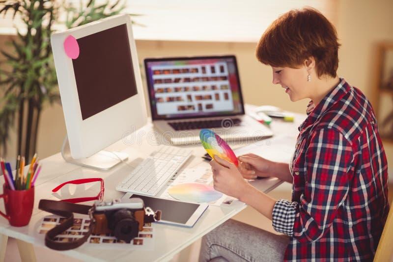 偶然女性设计师与数字化器和颜色图表一起使用 库存照片