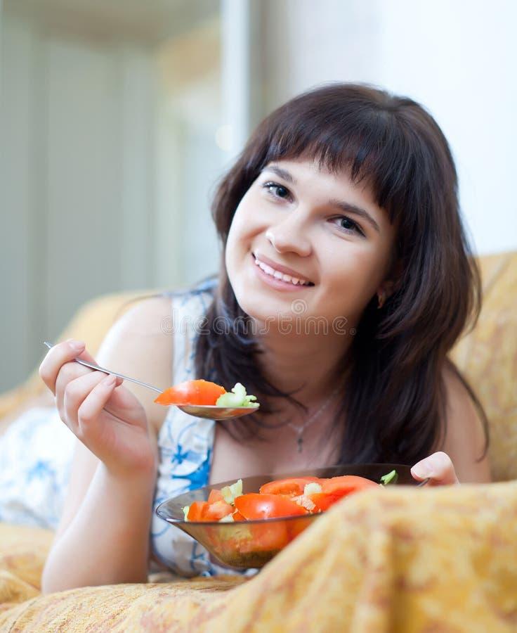 偶然妇女吃蕃茄沙拉 免版税图库摄影