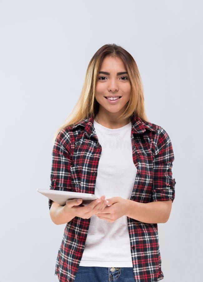 偶然妇女愉快的微笑年轻Asain女孩举行片剂计算机穿戴检查了被隔绝的衬衣 库存图片