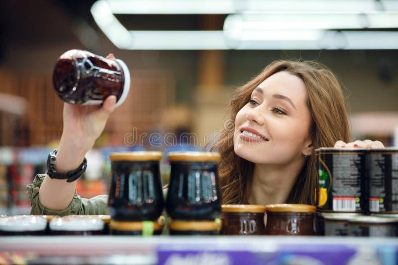 年轻偶然妇女采摘杂货在超级市场 库存照片