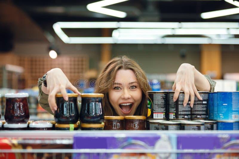 年轻偶然妇女采摘杂货在超级市场 免版税库存照片