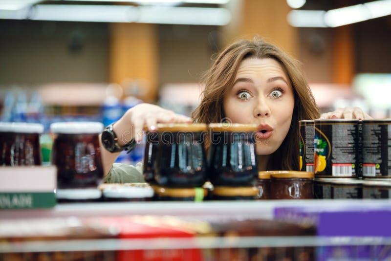 年轻偶然妇女采摘杂货在超级市场 图库摄影