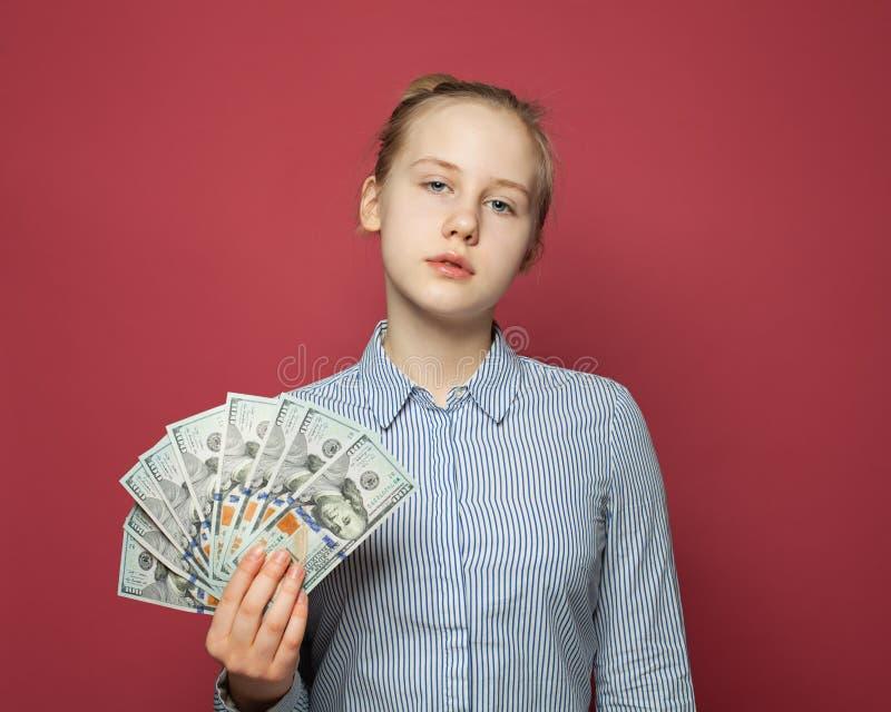 偶然少年女孩和金钱在桃红色背景 免版税图库摄影