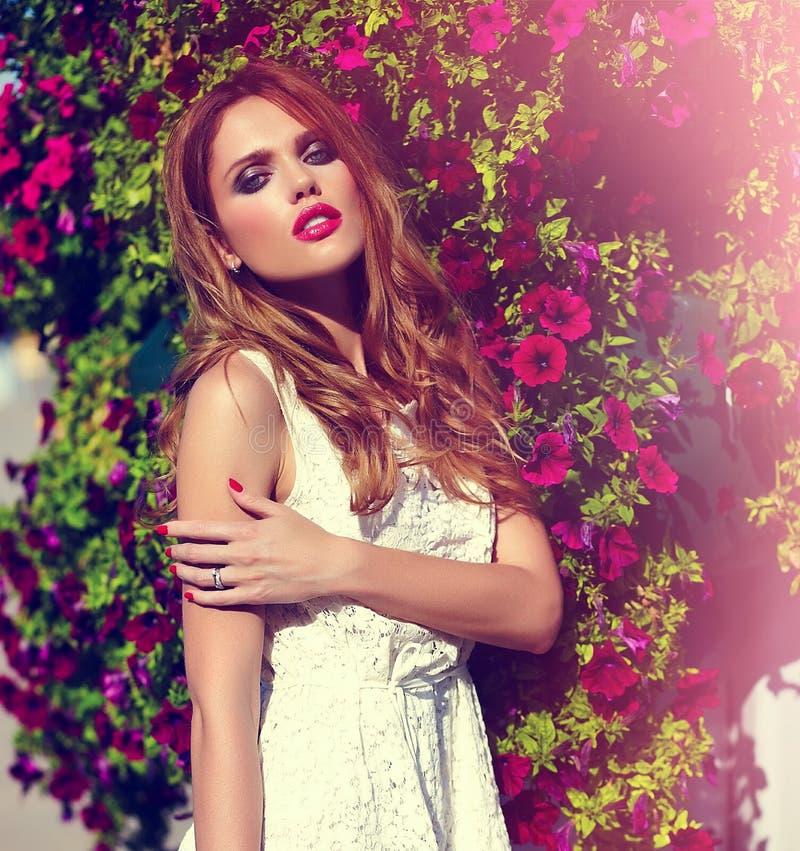 偶然布料的生活方式白肤金发的式样女孩在与桃红色嘴唇的花附近 库存照片