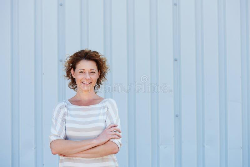 偶然愉快的有横渡的胳膊的妇女支持的墙壁 库存照片