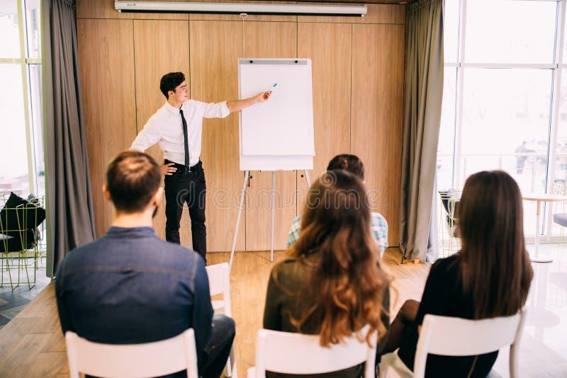 偶然成套装备的听一个总经理的年轻办公室工作者背面图解释某事使用例证 免版税库存图片