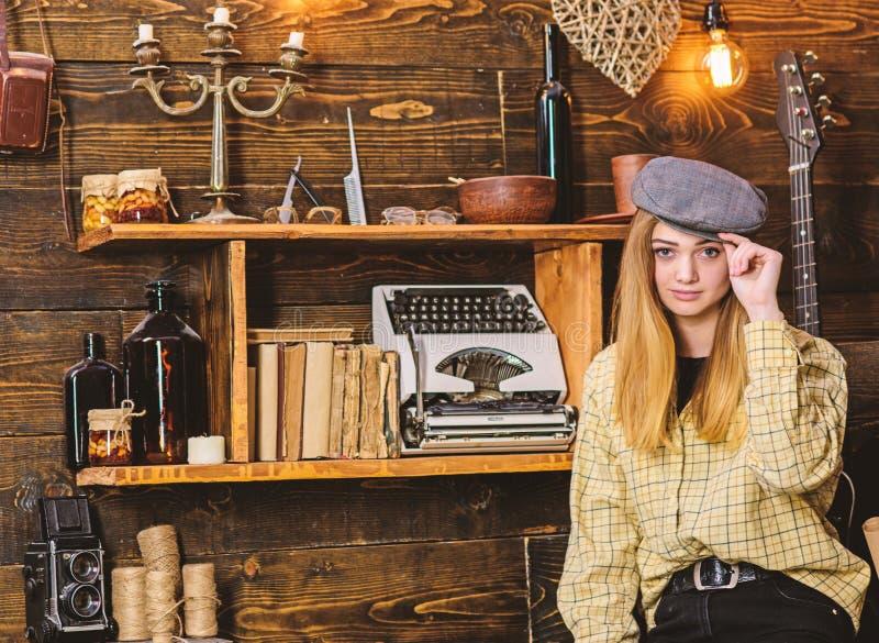 偶然成套装备的女孩有在木葡萄酒内部的平顶帽的 镇静面孔的夫人在格子花呢披肩衣裳看起来逗人喜爱和偶然 免版税图库摄影