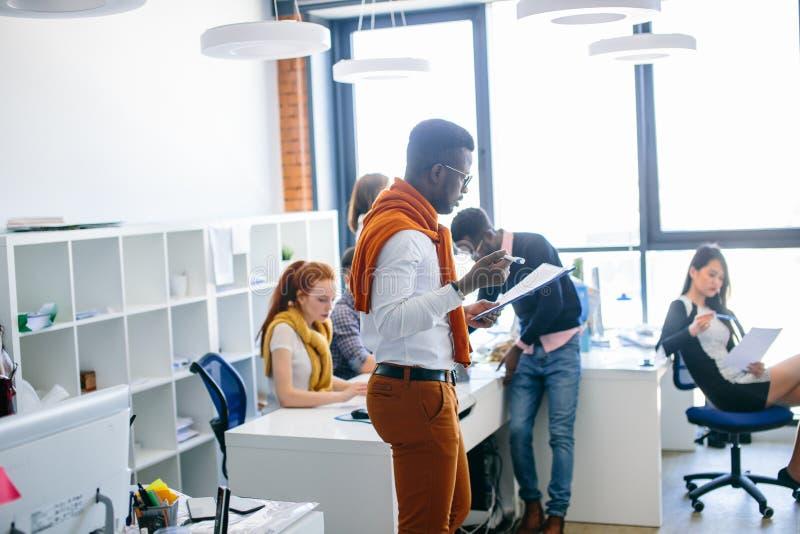 偶然成套装备的年轻精力充沛的办公室工作者读重要纸的 免版税库存照片