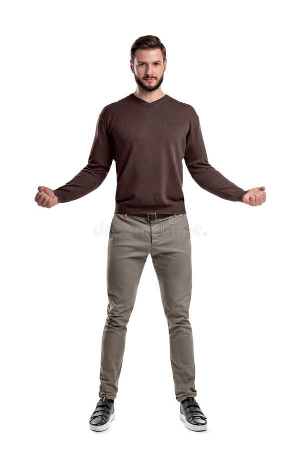 偶然服装的一个有胡子的人站立与他的胳膊提供宽与在紧的拳头的手指在一张正面图 库存图片