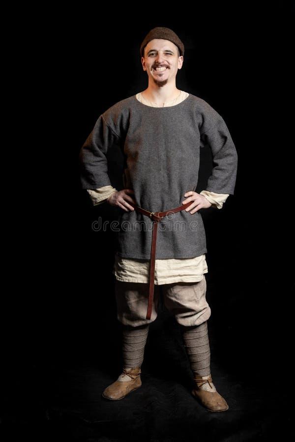 偶然灰色衣裳和北欧海盗年龄早中世纪闪光的帽子的年轻愉快的人 图库摄影