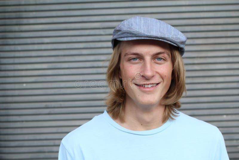 偶然白肤金发的年轻人佩带的新闻送报人帽子和蓝色水手领T恤杉画象  库存图片