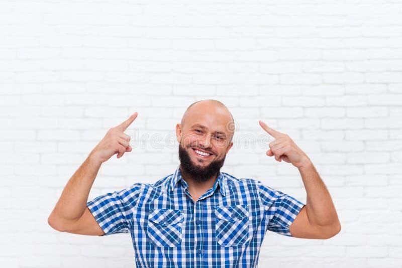 偶然秃头有胡子的商人微笑的点手指上升头 库存照片