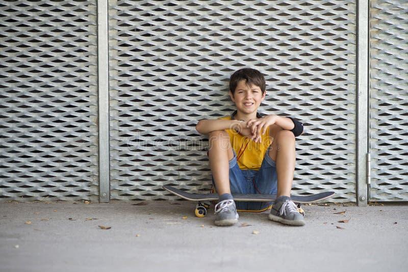 偶然穿戴的年轻人微笑的青少年的溜冰者户外画象 免版税库存照片