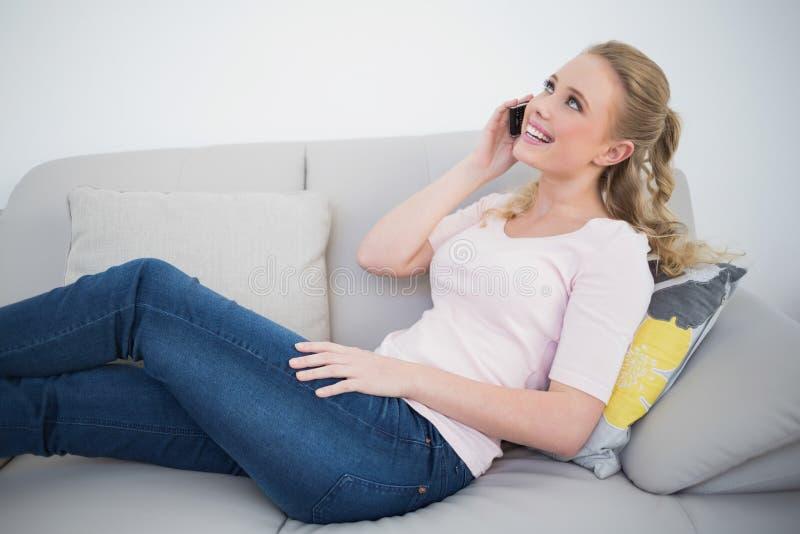 偶然笑的白肤金发打电话和说谎在长沙发 免版税库存图片