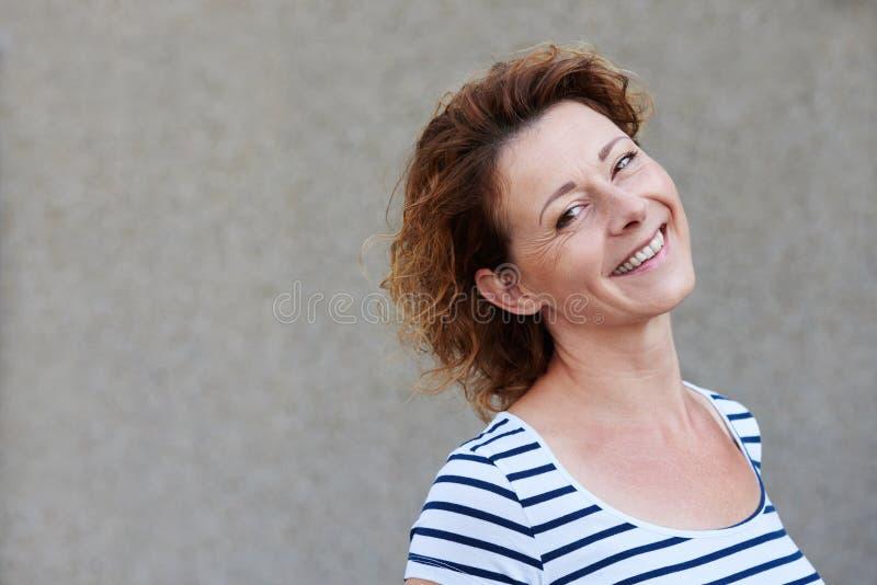 偶然老妇人支持的墙壁微笑 免版税库存照片