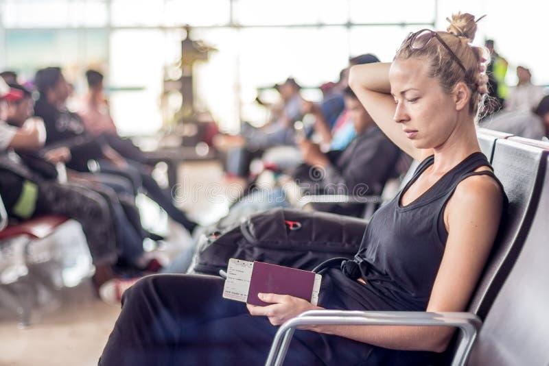 偶然被晒黑的白肤金发的女性旅客固定的单元电话、护照和登机牌,当等待上飞机在时 免版税库存图片