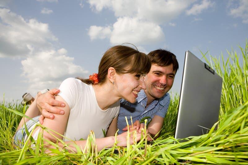 偶然计算机夫妇愉快的膝上型计算机 免版税库存图片