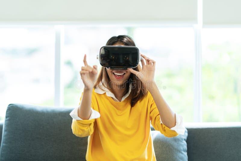 偶然黄色衬衣的年轻亚裔妇女戴VR眼镜观看录影的或喜欢演奏感觉的计算机游戏激发 免版税图库摄影