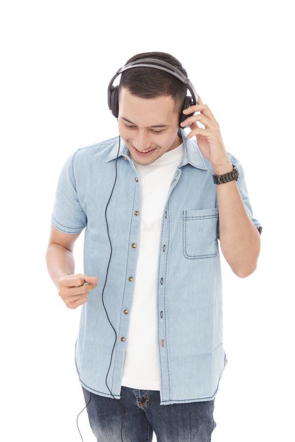 偶然年轻人享用音乐佩带的耳机 免版税库存照片