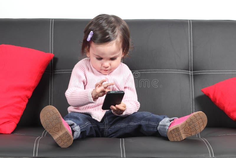 偶然婴孩坐接触一个手机的长沙发 免版税图库摄影