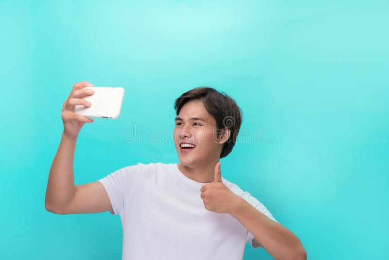 偶然T恤杉的帅哥微笑在与赞许的照相机的,当采取selfie时 库存照片