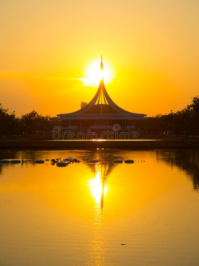 偶象大厦的完善的反射在水池的Suan的Luang Rama IX停放,泰国的地标有美丽的日落天空的 库存图片