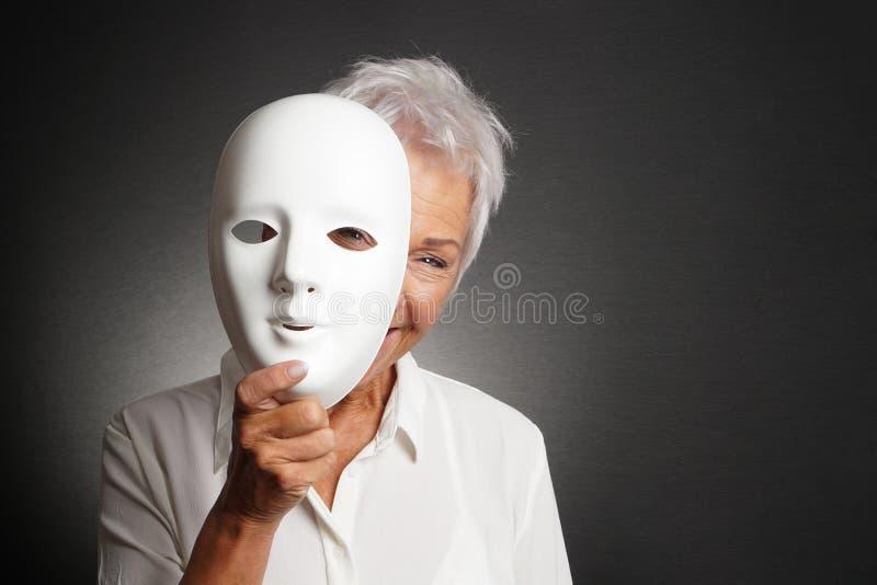 偷看从后面面具的愉快的资深妇女 免版税库存图片