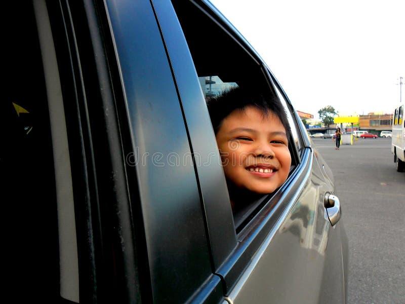偷看或看车窗的年轻男孩 图库摄影
