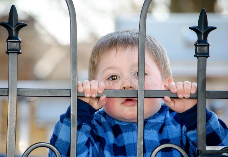 偷看通过门的小孩 免版税库存图片