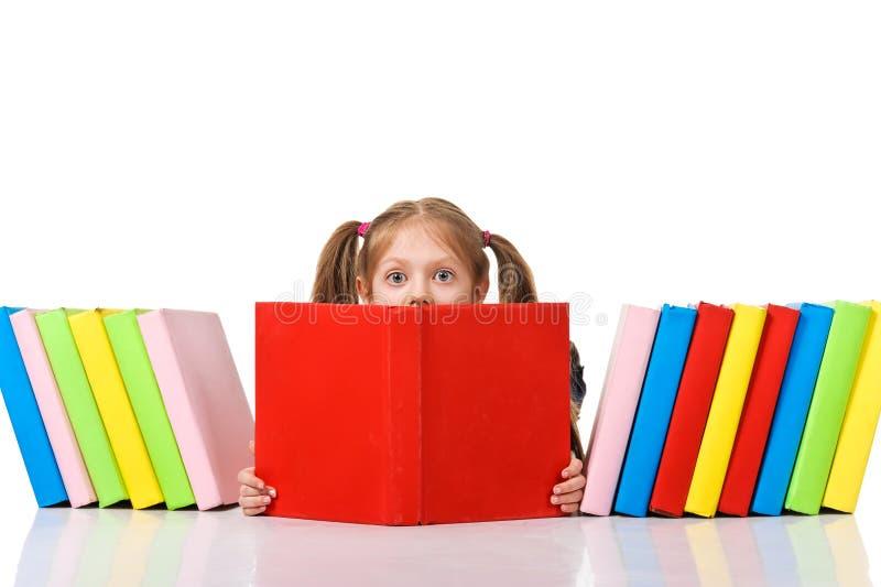 偷看从堆的小女孩书。 隔绝 库存照片