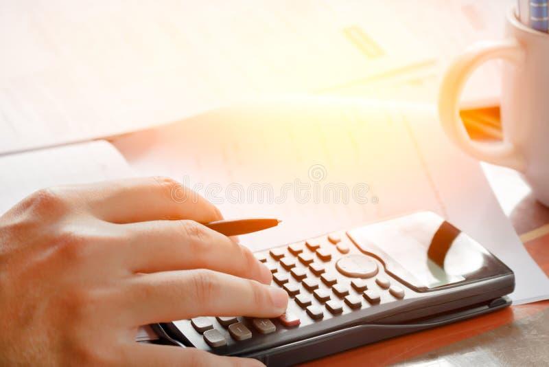 储款、财务、经济和家庭概念-接近有计数的计算器的人在家做笔记 库存图片