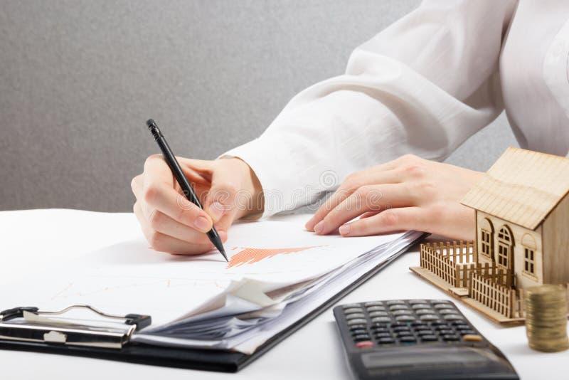 储款、财务、经济和家庭预算概念-接近计数在计算器损失的妇女,创造效益 库存图片