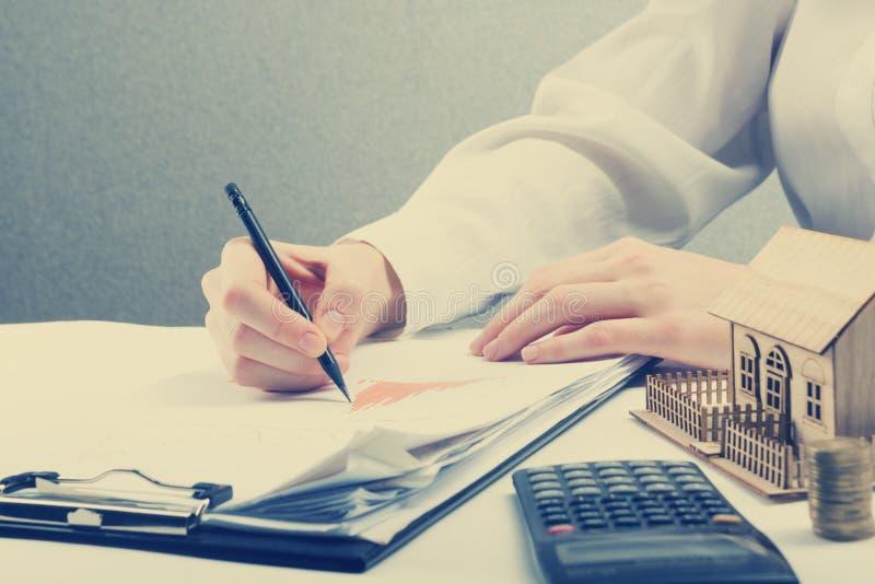 储款、财务、经济和家庭预算概念-接近计数在计算器损失的妇女,创造效益 免版税库存图片