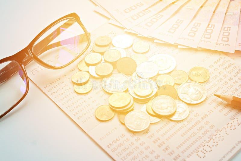 储蓄帐户存款簿、泰国金钱、硬币、眼睛玻璃和铅笔在蓝色背景 免版税库存照片